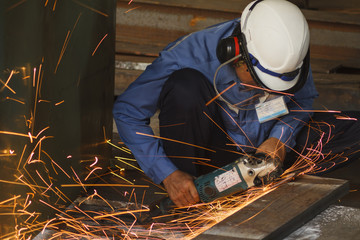 Worker with the face guard and electric wheel grinding on steel plate in factory. Heavy work concept.