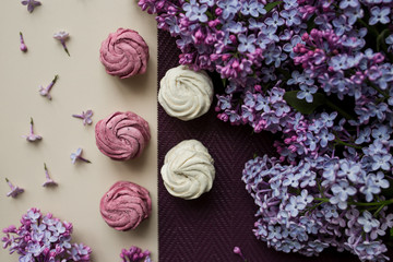 Pink and white marshmallows on a table with lilac flowers. Sweets and food in the kitchen.