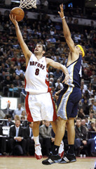 Toronto Raptors' guard Jose Calderon puts up a shot against Memphis Grizzlies' forward Andre Brown in Toronto