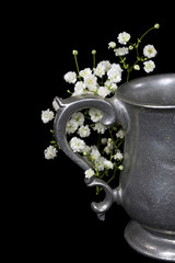 vintage pewter pitcher with white baby's breath on black