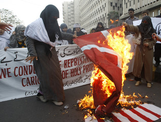 Activists from Imamia Students Organisation burn Danish and U.S. flags during a protest in Karachi