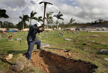 A grave digger uses a pickaxe to unearth a new grave at Lakeview Cemetery in Nassau