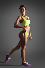 Muscular young woman athlete standing looking back on grey background