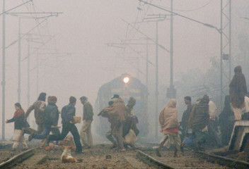 INDIAN'S CROSS THE RAILWAY TRACKS ON A FOGGY DAY IN PATNA.