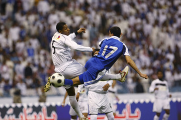 Al Hilal's Fahad Al Majraj (R) fights for the ball with al