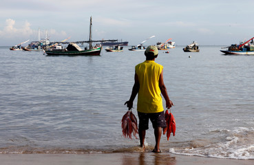 A fisherman holds fish at Meireles beach in Fortaleza