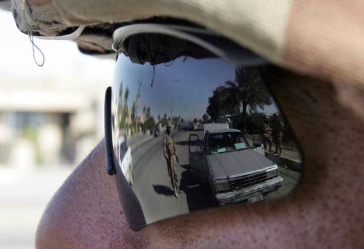 Iraqi soldiers are reflect on sunglasses as they conduct security checks at highway in Baghdad
