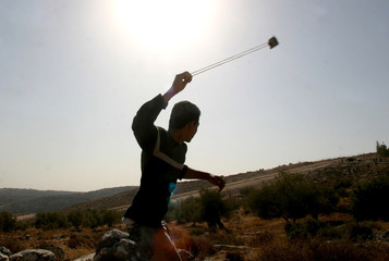 A Palestinian youth throws a stone at Israeli troops in Bilin