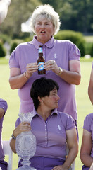 Davies, team member of European Solheim Cup, jokes around with bottle of beer over team captain Nicholas during team pictures in Sugar Grove