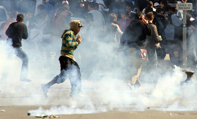 Demonstrators run away from tear gas thrown by police during a protest against the CPE in Marseille