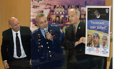 Canadian billionaire Laliberte, Russian cosmonaut Surayev and U.S. astronaut Williams show their cartoon before a news conference at Baikonur cosmodrome