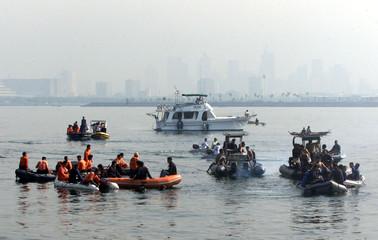 FILIPINO RESCUERS SEARCH FOR PLANE CRASH SURVIVORS IN MANILA BAY.