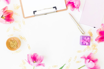 Beauty blog concept. Round frame. Workspace with clipboard, notebook, pen, pink tulip flowers and accessories on white background. Flat lay, top view. Blogger or freelance