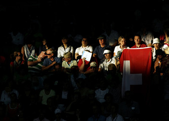 Fan of  Federer holds Swiss flag during Federer's semi-final match against Serbia's Djokovic at the Australian Open tennis tournament in Melbourne