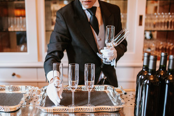 Waiter placing champagne flutes on silver tray