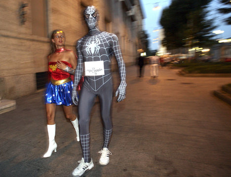 People dressed in costumes of fictional superheroes conduct a mock security patrol in Milan