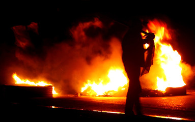 Resident of San Salvador Atenco stands guard at a road block of burning tyres, at the entrance to Atenco near Mexico City