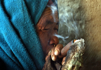 Nepali woman smokes from an earthen pipe in the village of Tila, western Nepal