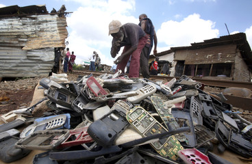 Charles Okada, a salvage merchant, organizes a pile of mobile phone parts at his open stall in Kenya's capital Nairobi