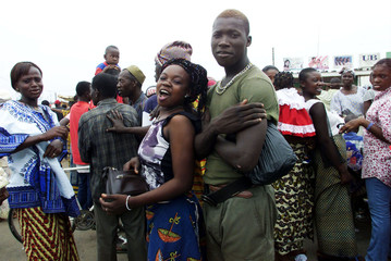 Rebel soldiers are surrounded by women in the rebel stronghold of Bouake, February 17, 2003.  [The c..