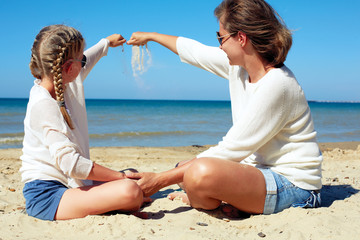 Daughter and her mom playing with sand on the beach