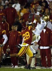 Notre Dame wide receiver McKnight makes a catch over USC defender Thomas in Los Angeles