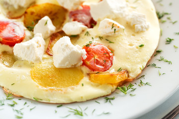 Delicious omelette with tomato, potato and goat cheese