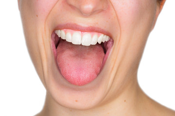 Closeup portrait of young woman with withe perfect teeth showing the tongue in a playful way