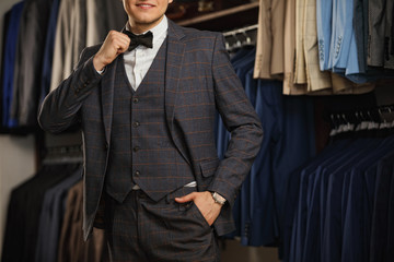 Businessman in classic vest against row of suits in shop. A young stylish man in a black cloth jacket. It is in the showroom, trying on clothes, posing. Advertising photo