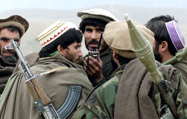 ANTI TALIBAN AFGHAN FIGHTERS LISTEN TO A WALKIE TALKIE IN THE TORA BORAMOUNTAINS.