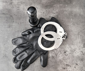 German police handcuffs, leather gloves and a torchlight on rough grey background with copy space. Top down View.