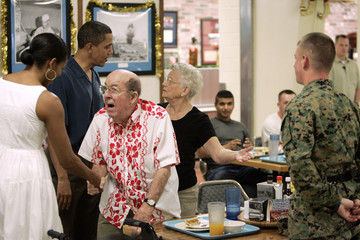 U.S. President Barack Obama and first lady Michelle Obama greet a military family who was having Christmas dinner at Anderson Hall on Marine Corps Base Hawaii in Kailua