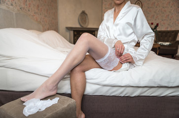 Beauty bride in a dress wearing stockings wedding indoors. Female portrait nice lady in a dress. Closeup of woman hands