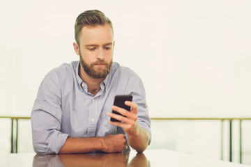 Serious Young Man Using Smartphone at Cafe Table