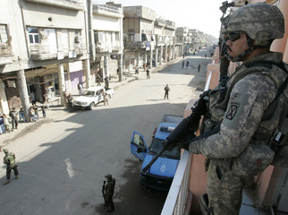 U.S. soldiers and members of U.S. backed neighbourhood patrol unit secure road in central Baghdad's Fadil district