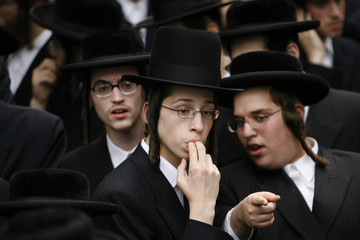 An Ultra-Orthodox Jewish man looks at where another is pointing during a protest against the Israeli government in New York