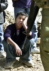 A PALESTINIAN BOY SITS IN FRONT OF AN ISRAELI SOLDIER AT THE QALANDIACHECKPOINT.