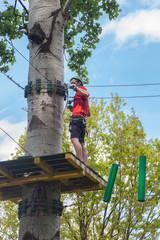 man in adventure park on  tree top
