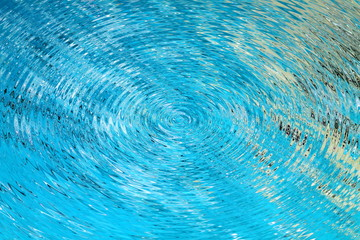 Swirling cyan blue pool fragment.  Wavy surface after water drop.