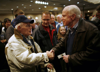 Presidential hopeful and US Senator McCain speaks with a supporter after a town hall meeting in Cedar Rapids
