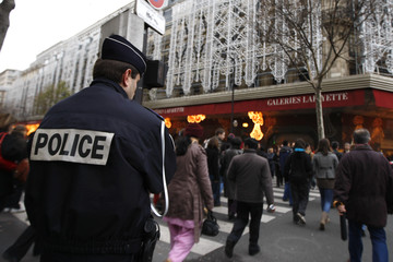 A French policeman surveys the Galerie Lafayette department store area in Paris