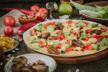 Vegetarian home made pizza with mushrooms and vegetables over wooden table, surrounded by ingredients