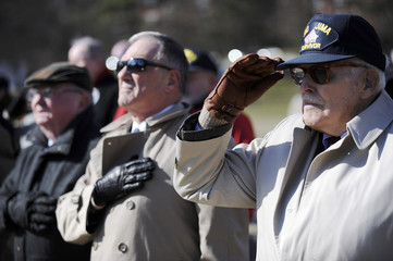 Veterans stand during the national anthem in honor the 64th anniversary of the raising of the US flag on the island of Iwo Jima during World War II, during a ceremony at the Marine Corps War Memorial in Arlington, Virginia
