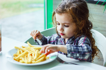 Little girl having lunch in the restaurant with the table knife and fork in hands.