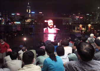MUSIC LOVERS ENJOY A LIVE BROADCAST RELAY OF THE CONCERT OF PAVAROTTI IN HONG KONG.
