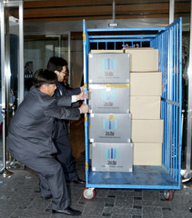Investigators from the prosecution office move boxes holding evidence seized at a local office of Lone Star in Seoul