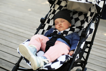 Cute baby in a hat asleep in a baby carriage