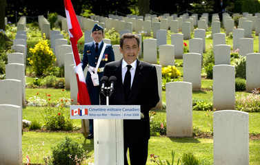France's President Sarkozy speaks during visit the Canadian military cemetery in Beny-Reviers
