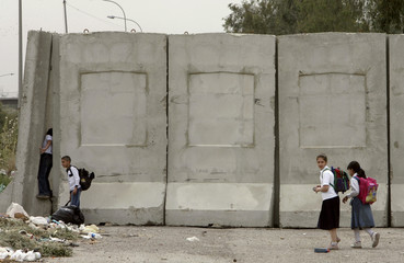 Schoolchildren pass concrete walls in Adhamiya district in Baghdad
