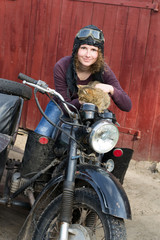 Photo of girl on a vintage motorbike in pilot cap with cat